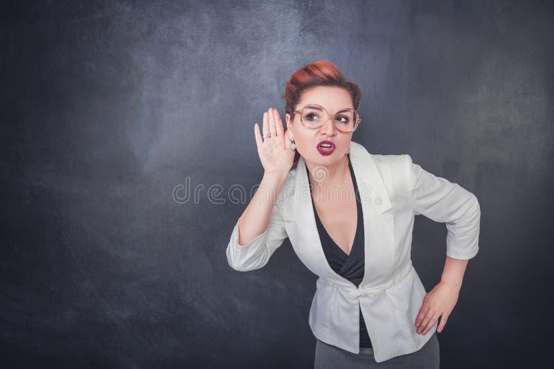 La mujer divertida escucha detras de las puertas en fondo de la pizarra fotografía de archivo