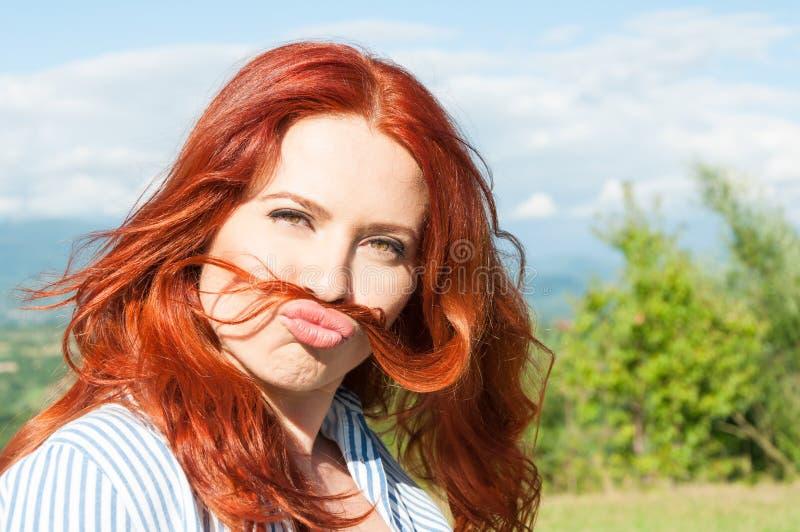 La mujer divertida muestra el pelo del bigote y la diversión el tener foto de archivo