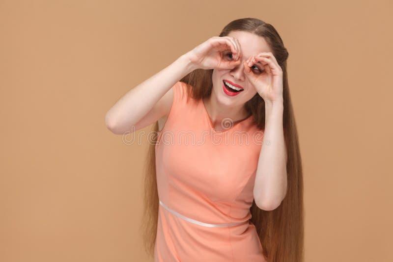 La mujer divertida sorprendente con los prismáticos da la mirada de la cámara foto de archivo