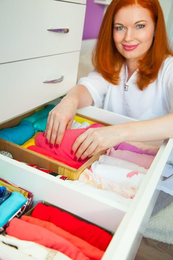 La mujer dobla las camisetas en el cajón Una mujer está ordenando el th foto de archivo libre de regalías