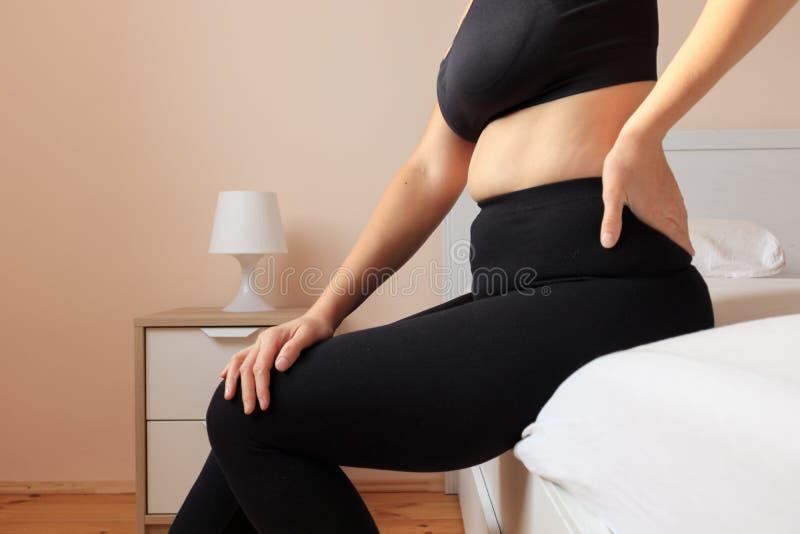 La mujer dolorosa está sintiendo dolor de espalda en dormitorio foto de archivo