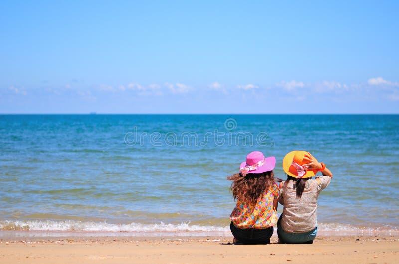 La mujer dos se sienta en la playa fotografía de archivo libre de regalías