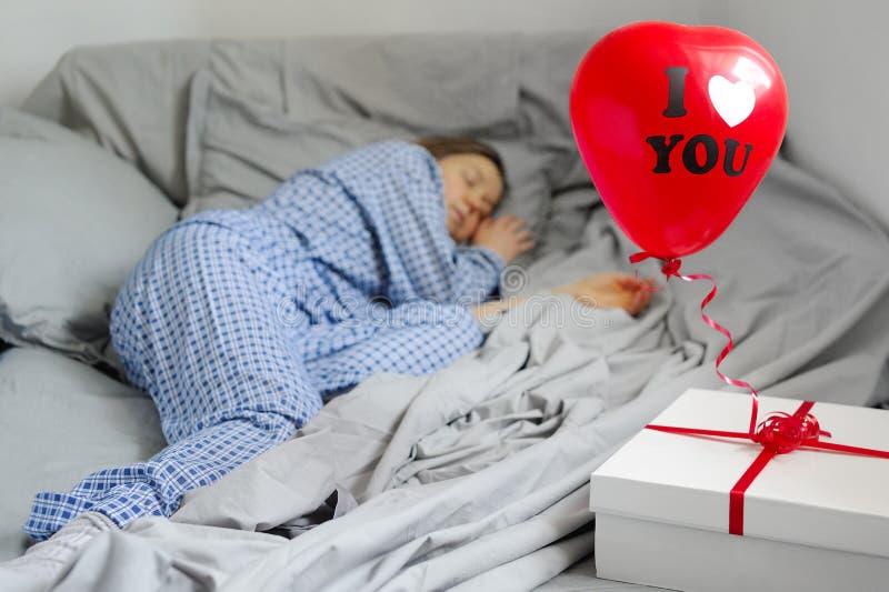 La mujer duerme en los pijamas, un regalo en la cama Día del `s de la tarjeta del día de San Valentín foto de archivo libre de regalías