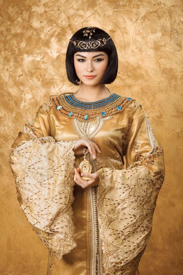La mujer egipcia hermosa le gusta Cleopatra con la botella de perfume en fondo de oro imagen de archivo libre de regalías