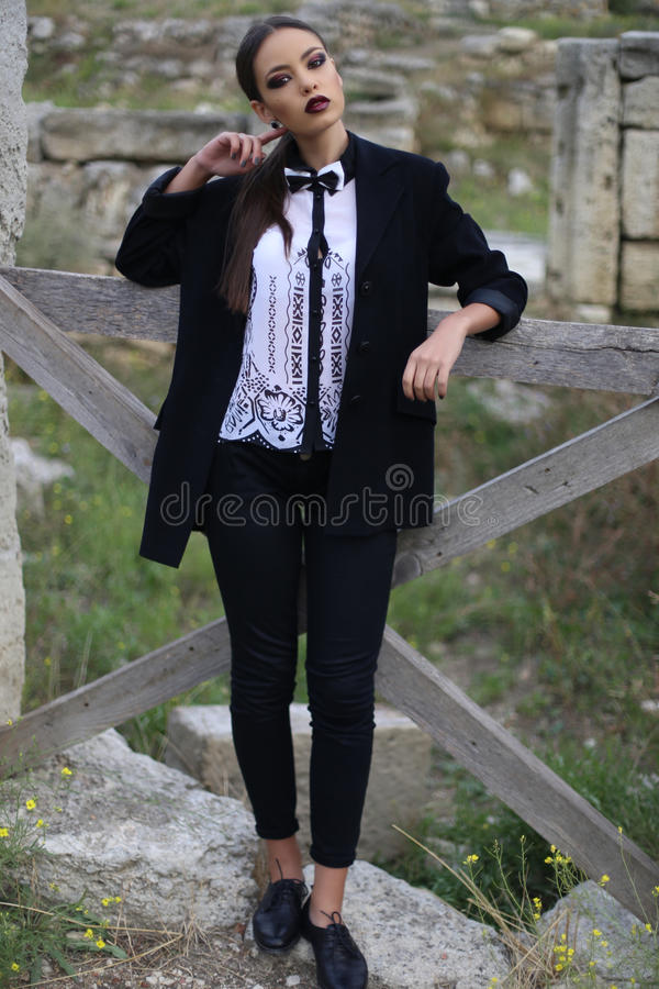 La mujer elegante atractiva con el pelo oscuro lleva la camisa blanca y los pantalones negros fotos de archivo
