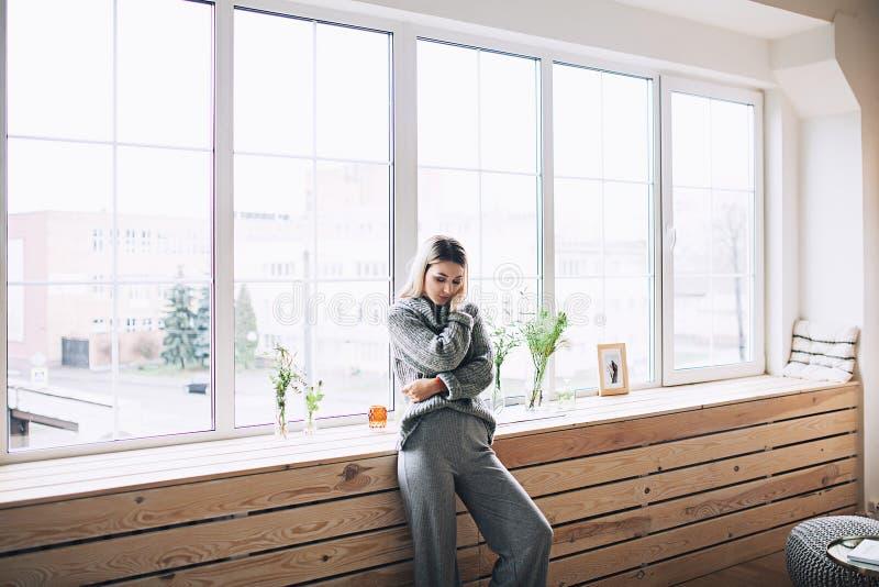 La mujer elegante blanca hermosa en interrior escandinavo acogedor se sienta en casa cerca de la ventana grande, retrato del herm imagen de archivo