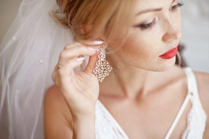 La mujer elegante del primer en la ropa interior blanca del cordón pone su pendiente foto de archivo libre de regalías