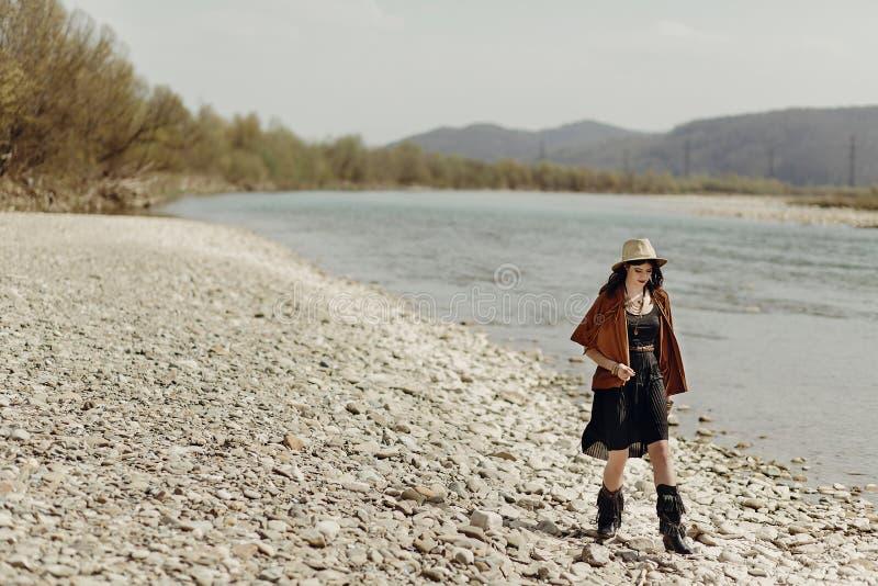 La mujer elegante del viajero del boho en sombrero, el poncho de la franja y las botas caminan fotos de archivo