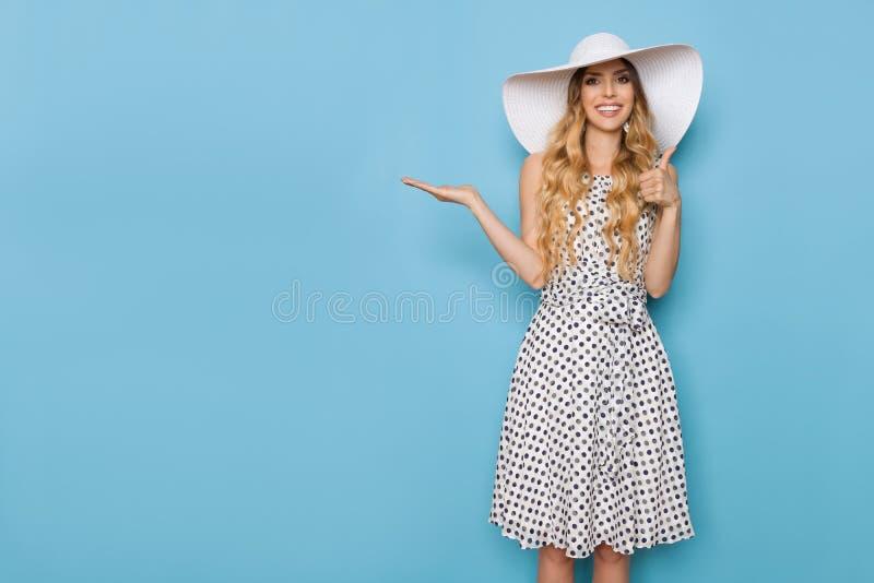 La mujer elegante en vestido del verano y el sombrero de Sun del blanco es presente, sonriente y que muestra el pulgar U imagenes de archivo
