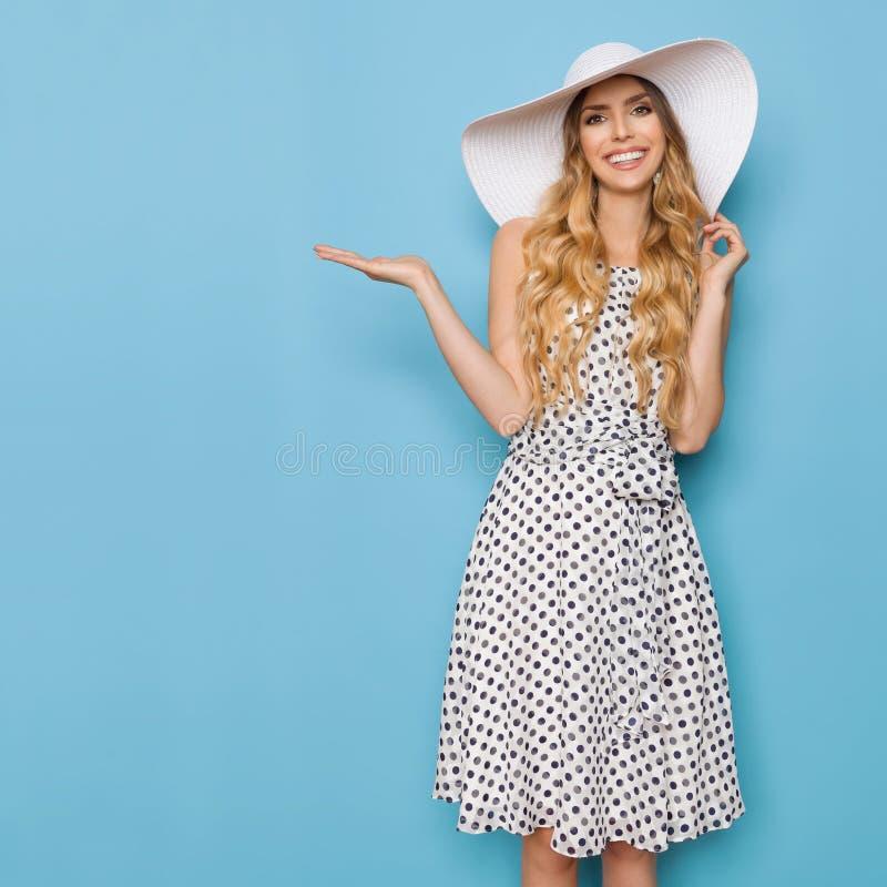 La mujer elegante en vestido del verano y el sombrero de Sun del blanco está presentando y está sonriendo imagenes de archivo