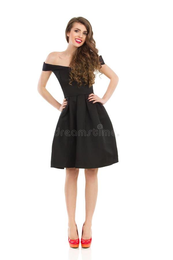 La mujer elegante en vestido negro está presentando con las manos en cadera fotos de archivo libres de regalías