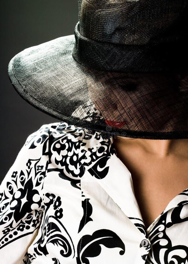 La mujer elegante está en un sombrero imagenes de archivo