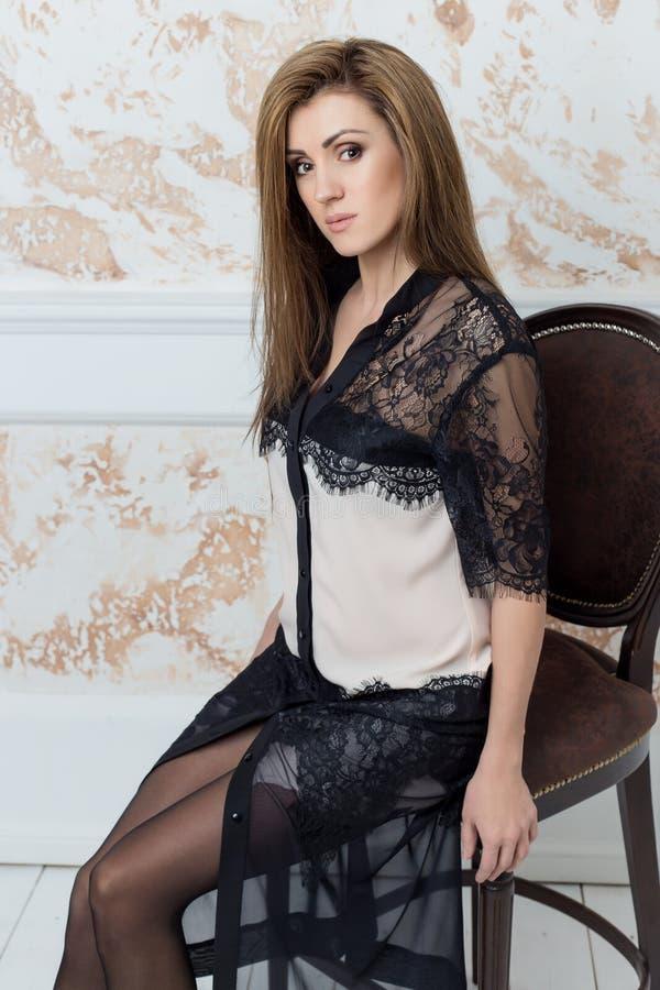 La mujer elegante hermosa con el pelo largo con un maquillaje apacible en el estudio muestra el vestido blanco elegante del negoc fotos de archivo