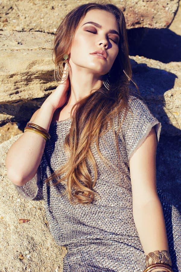 la mujer elegante hermosa con el pelo largo se vistió en la presentación en las rocas foto de archivo libre de regalías