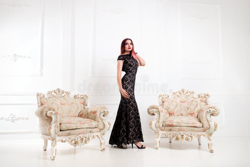 La mujer elegante o la muchacha en la igualación del vestido negro se está colocando en una a imágenes de archivo libres de regalías