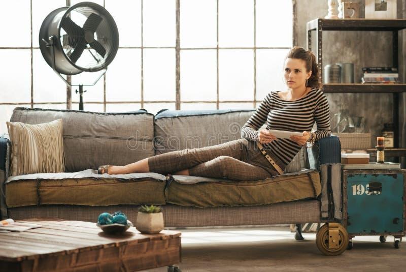 La mujer elegante pensativa se está sentando en el sofá y está sosteniendo la tableta imágenes de archivo libres de regalías