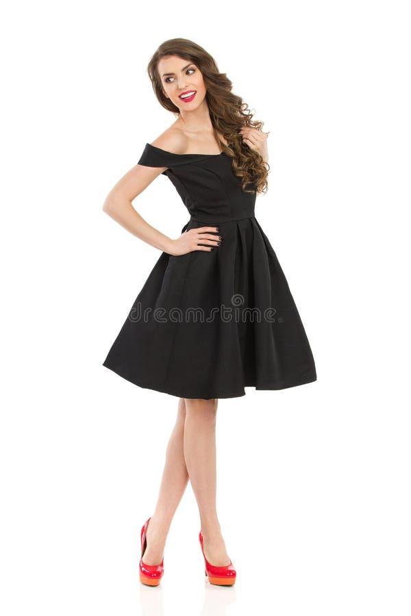 La mujer elegante sonriente en vestido de cóctel negro está mirando lejos fotos de archivo libres de regalías