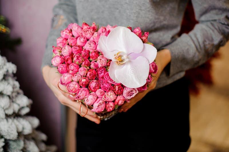 La mujer elegante sostiene un ramo con muchas pequeñas rosas y una orquídea grande imagen de archivo