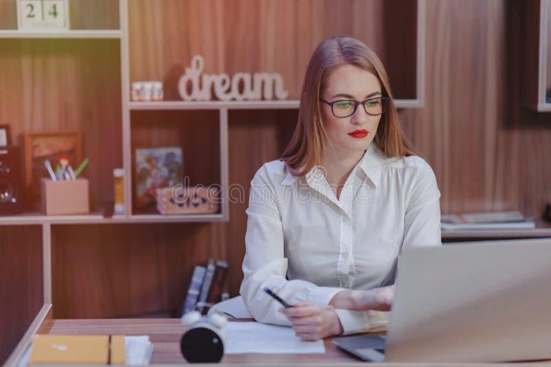 La mujer elegante trabaja en un escritorio del ordenador port?til en una oficina moderna fotos de archivo libres de regalías