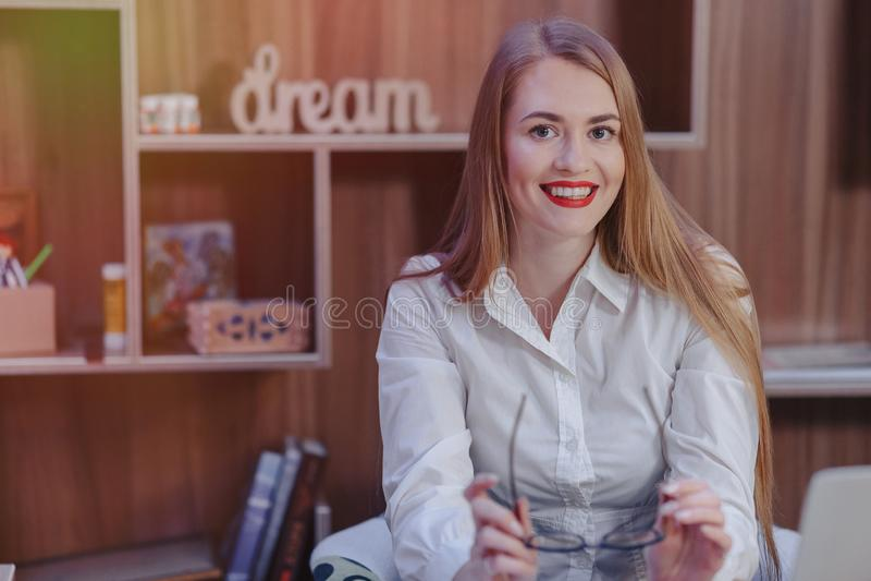 La mujer elegante trabaja en un escritorio del ordenador port?til en una oficina moderna fotografía de archivo libre de regalías