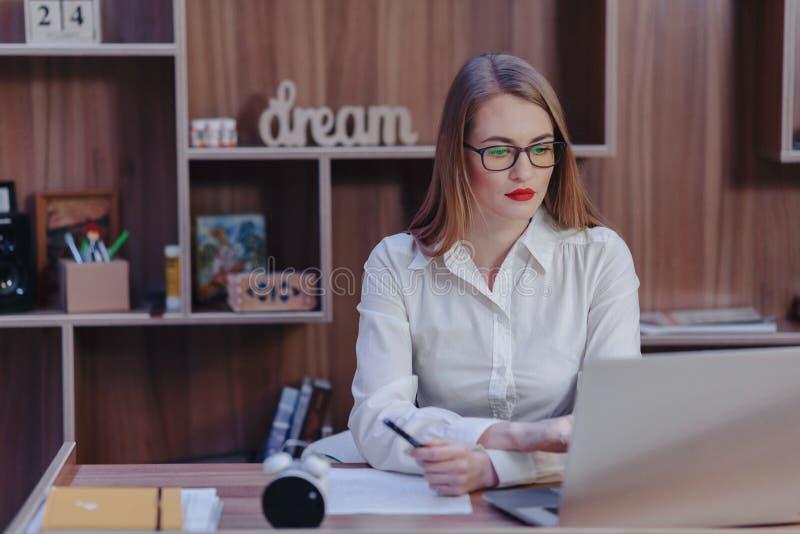 La mujer elegante trabaja en un escritorio del ordenador port?til en una oficina moderna fotos de archivo