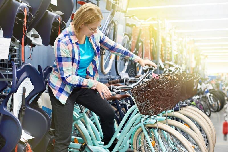 La mujer elige la bicicleta en tienda imagenes de archivo