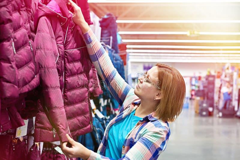 La mujer elige la chaqueta del invierno en tienda fotografía de archivo libre de regalías