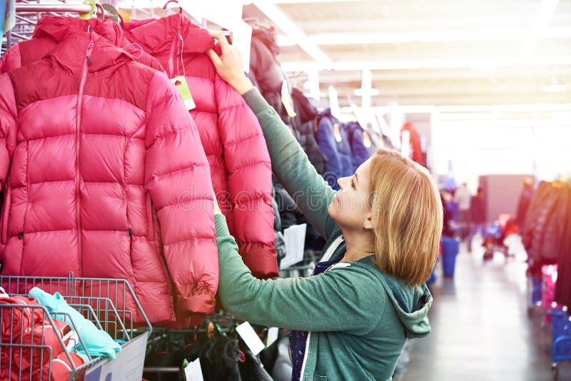 La mujer elige la chaqueta del invierno en tienda imágenes de archivo libres de regalías
