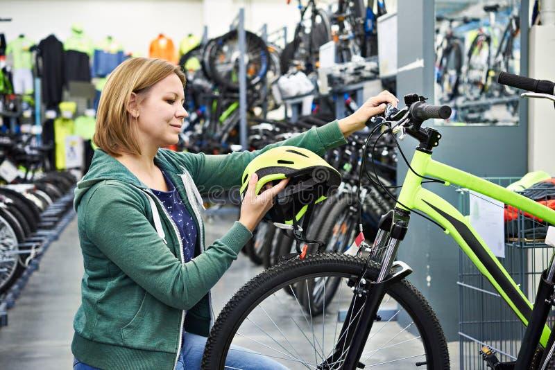 La mujer elige el casco para completar un ciclo en tienda imagenes de archivo