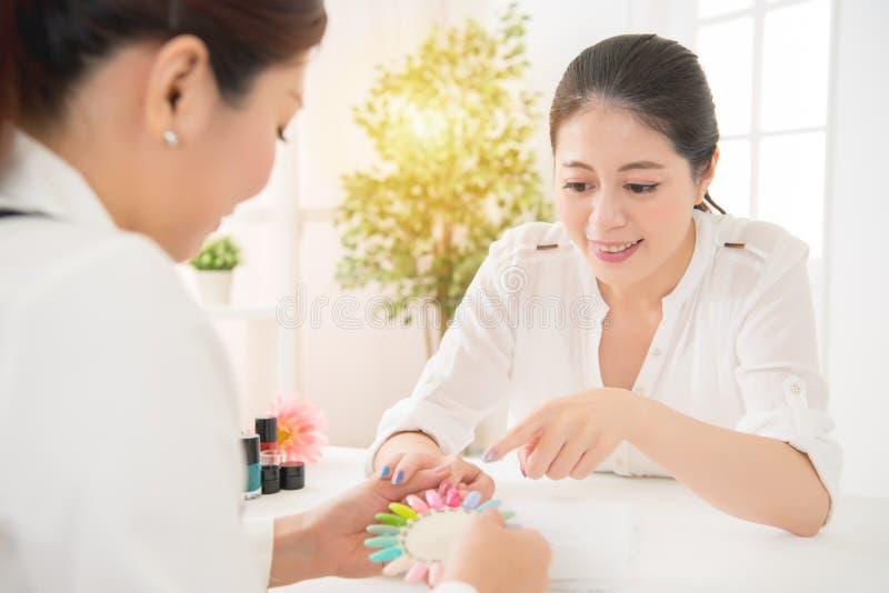 La mujer elige esmalte de uñas colorido de la manicura foto de archivo