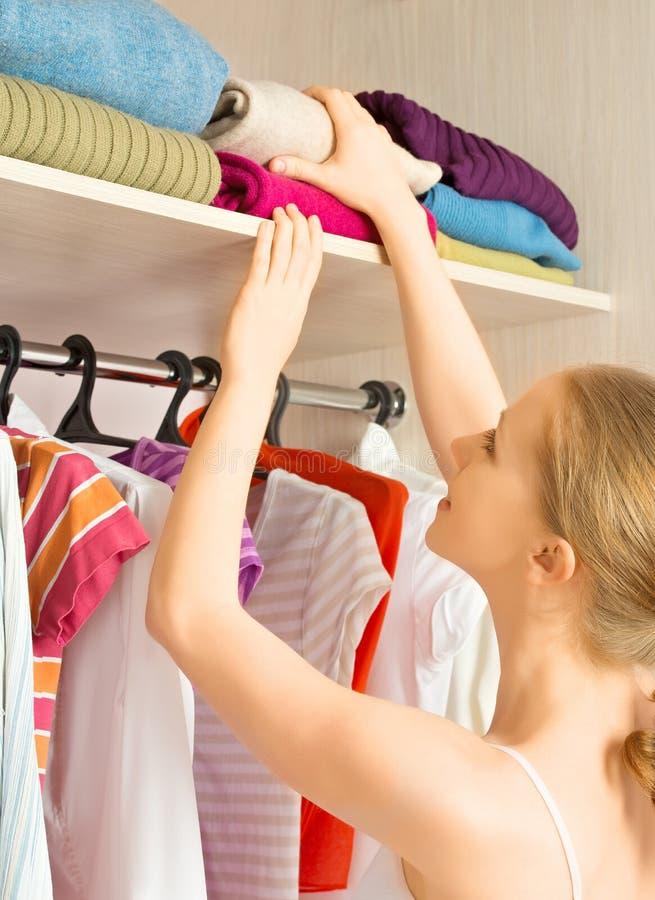 La mujer elige la ropa en el armario del guardarropa en casa imagen de archivo libre de regalías