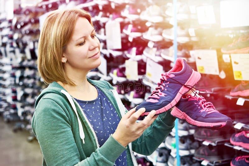 La mujer elige las zapatillas deportivas en tienda fotografía de archivo libre de regalías