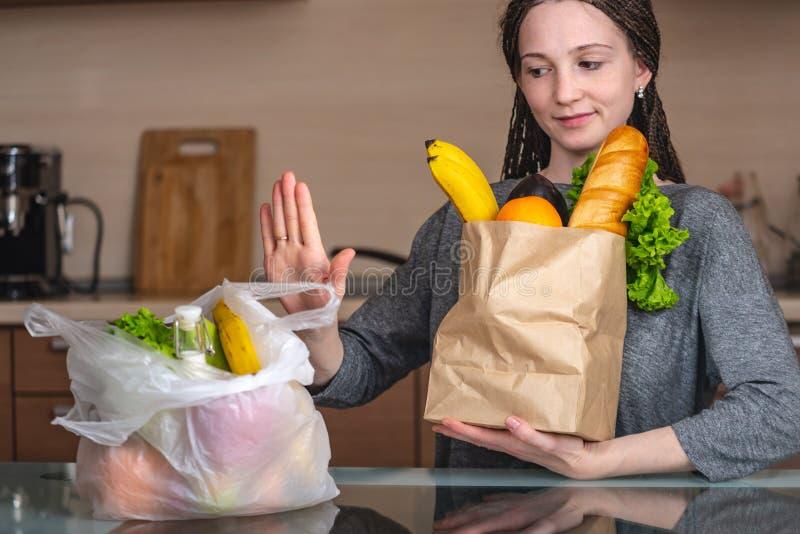 La mujer elige una bolsa de papel con la comida y rechaza utilizar el plástico Concepto de protecci fotos de archivo