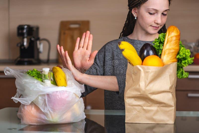 La mujer elige una bolsa de papel con la comida y rechaza utilizar el plástico Concepto de protecci imagen de archivo libre de regalías