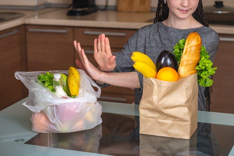 La mujer elige una bolsa de papel con la comida y rechaza utilizar el plástico Concepto de protecci foto de archivo