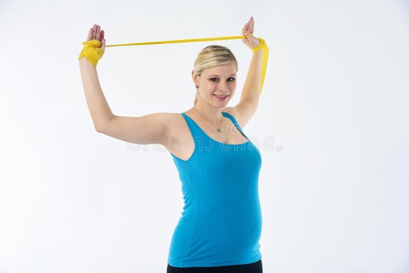 La mujer embarazada blondy joven en camisetas sin mangas azules hace ejercicios con la goma de la aptitud amarilla, fondo blanco fotografía de archivo libre de regalías