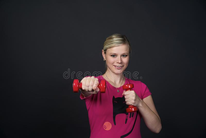 La mujer embarazada blondy joven en t-cortocircuito rosado con el gato hace ejercicios con las pesas de gimnasia rojas de la apti imagen de archivo libre de regalías
