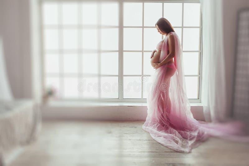 La mujer embarazada de los jóvenes en tela rosada está haciendo una pausa la ventana Tiro irreconocible del estudio de la mujer e imagen de archivo libre de regalías