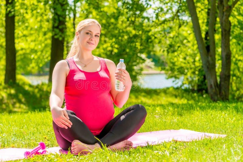 La mujer embarazada de los jóvenes tiene un resto que se sienta en una estera imagen de archivo libre de regalías