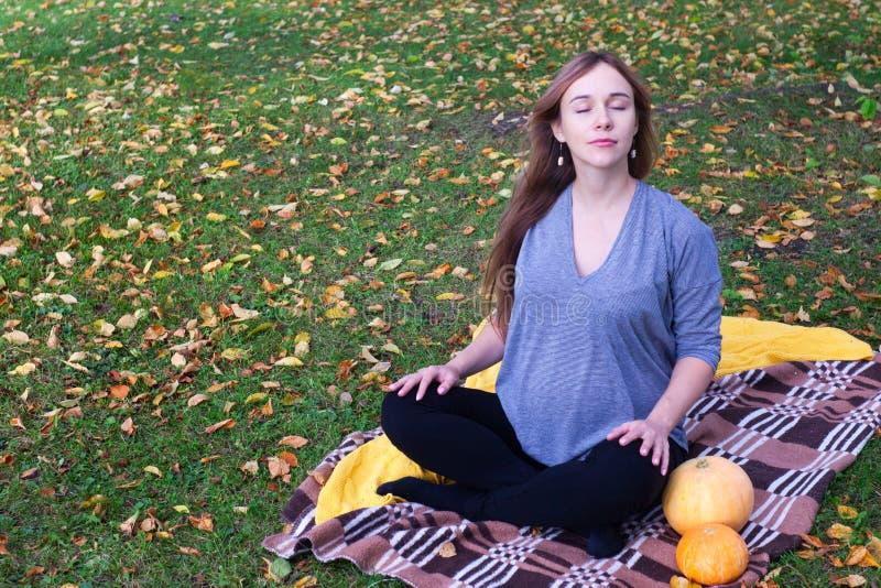 La mujer embarazada de la yoga con la tela escocesa y el retrato de las calabazas en otoño parquean en la hierba, respiración, es foto de archivo libre de regalías
