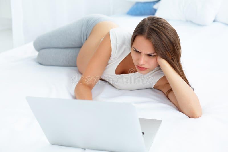 La mujer embarazada deprimida trabaja en el ordenador portátil mientras que miente encendido fotografía de archivo