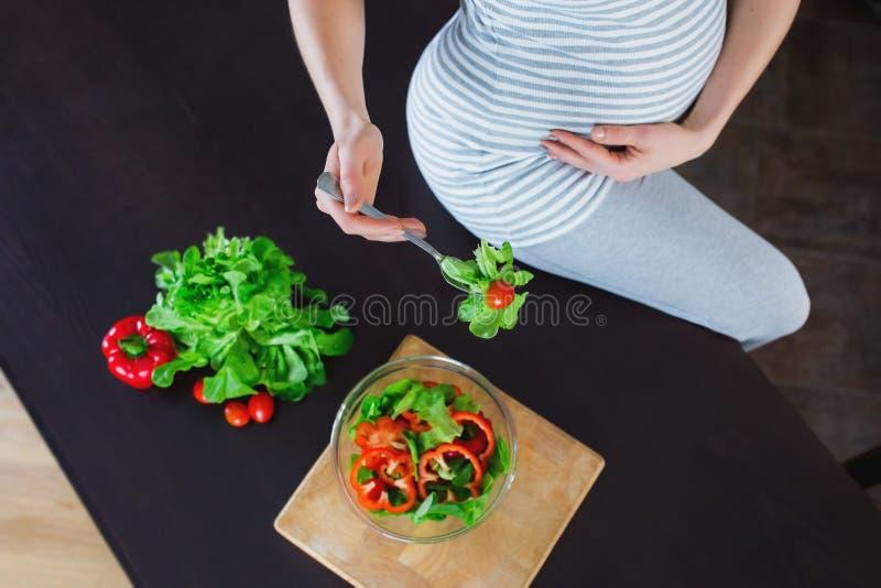 La mujer embarazada en cocina está comiendo la ensalada vegetal fotos de archivo
