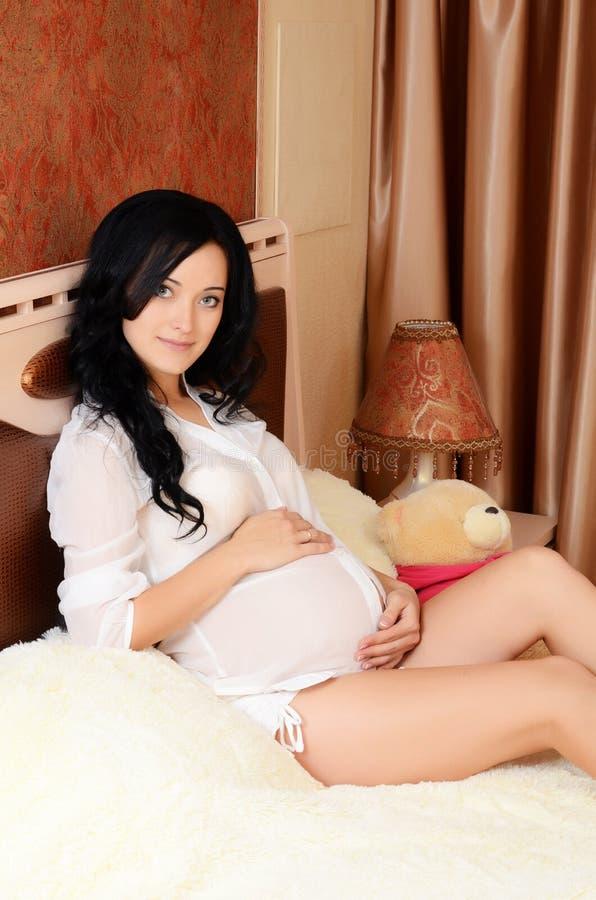 La mujer embarazada en una cama en un cuarto foto de archivo