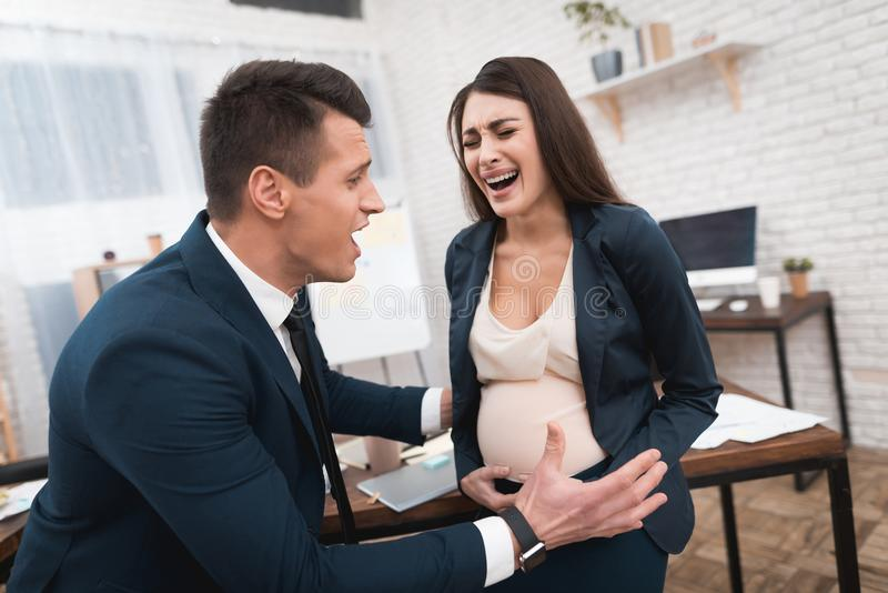 La mujer embarazada está experimentando el trabajo en oficina La chica joven está dando a luz en oficina imagenes de archivo