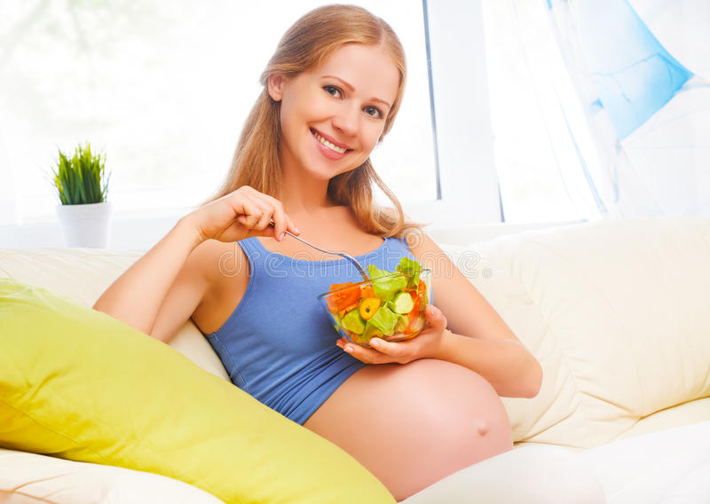 La mujer embarazada feliz come la ensalada sana de la verdura de la comida fotos de archivo libres de regalías