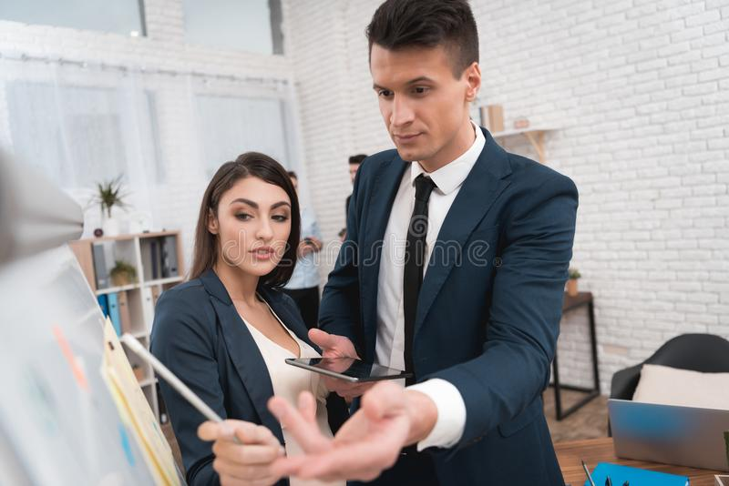 La mujer embarazada hermosa con el hombre joven en traje está estudiando cartas y diagramas en flipchart fotos de archivo libres de regalías