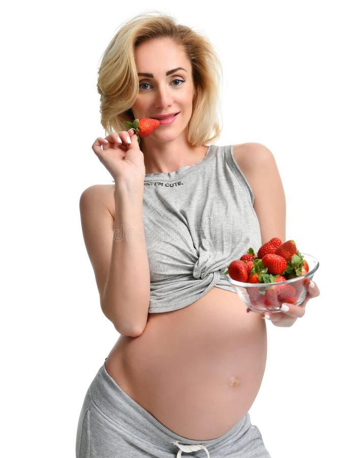 La mujer embarazada hermosa con el vientre grande come el strawberrie imagenes de archivo