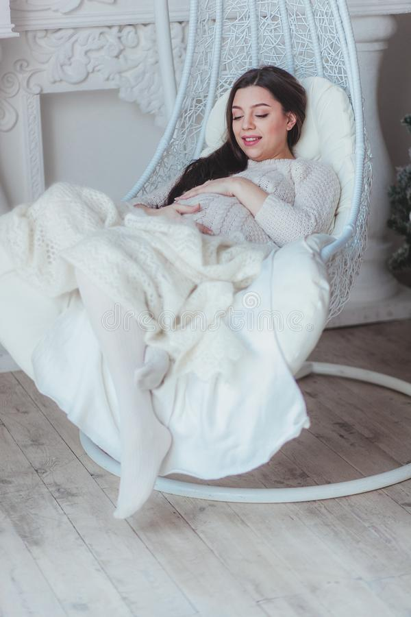 La mujer embarazada hermosa que se sienta en el capullo de mimbre preside en casa foto de archivo libre de regalías