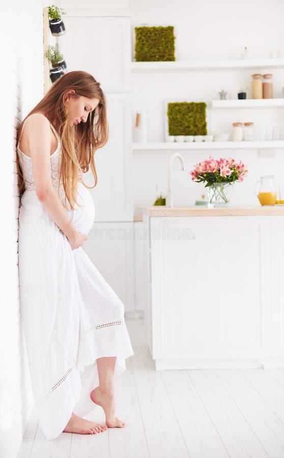 La mujer embarazada joven hermosa en verano con volantes se viste en casa imagen de archivo