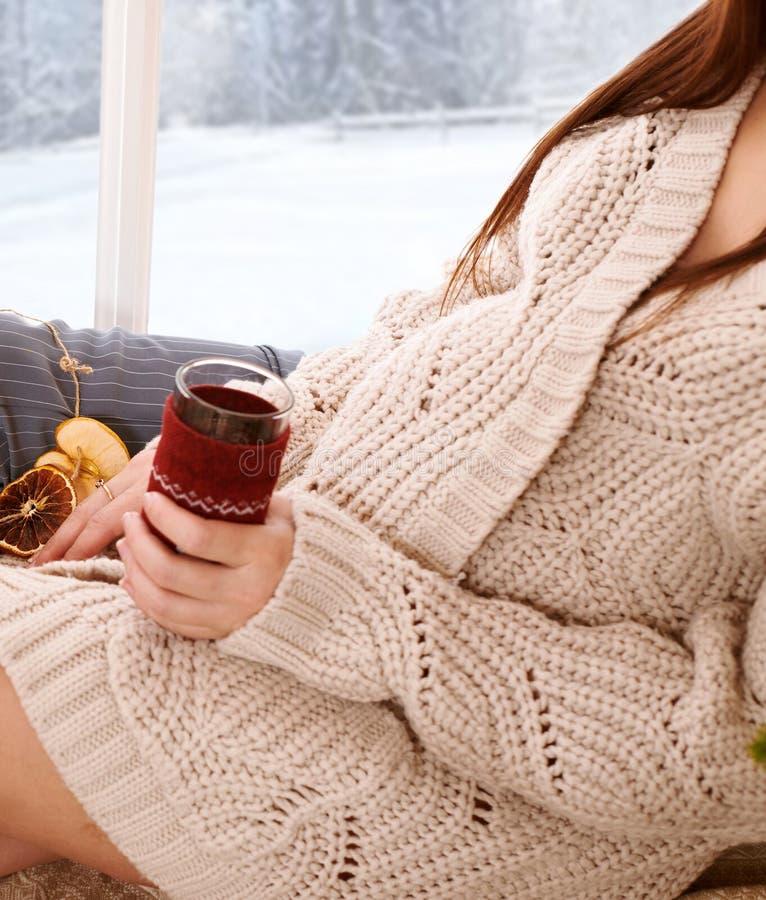 La mujer embarazada que se sienta cerca de la ventana y del té de consumición, paisaje hermoso del invierno con el bosque nevoso  imagen de archivo libre de regalías